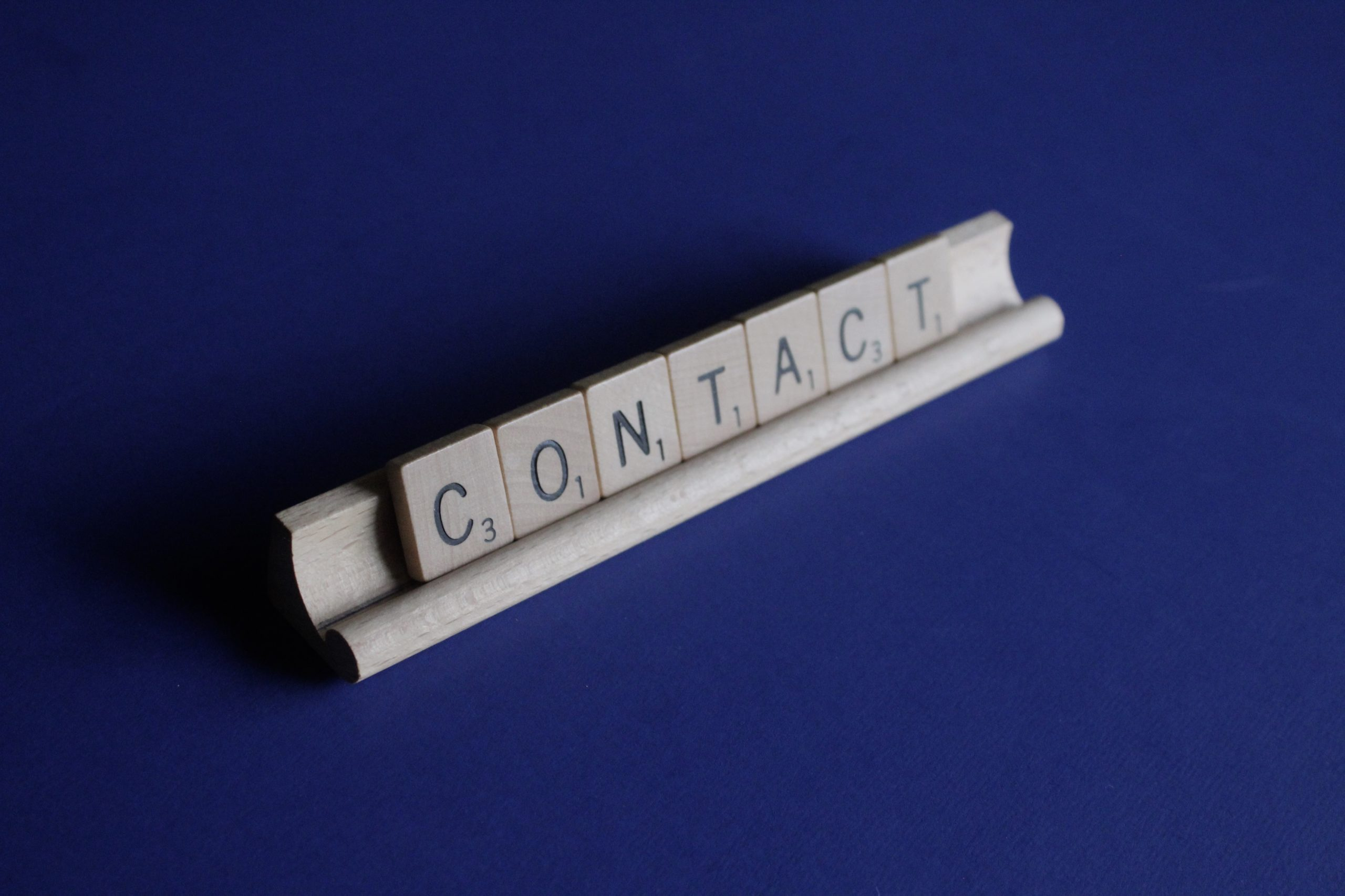 Contact spelled with Scrabble Letters